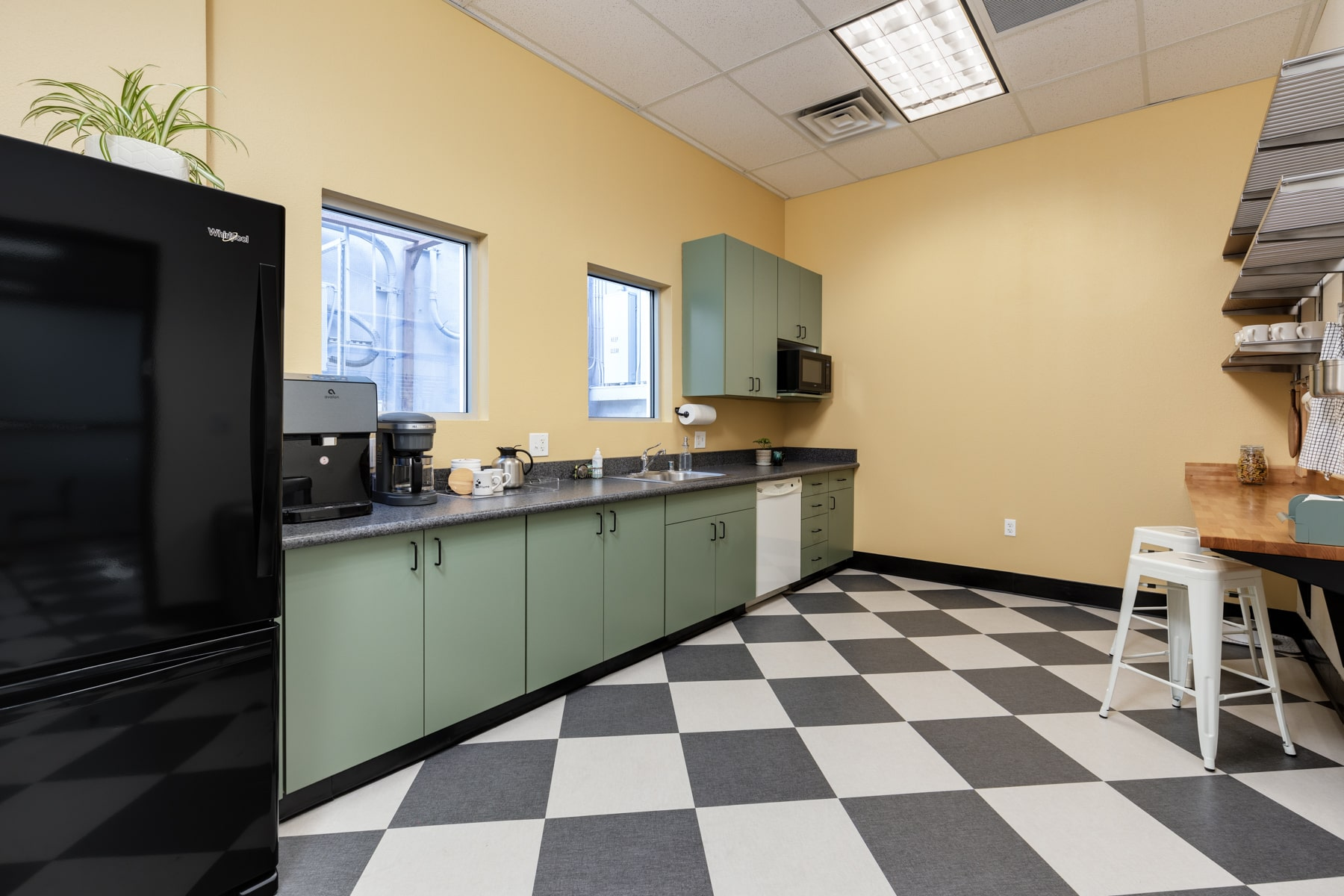 A large, open kitchen with white and black checkered tiles, a lot of counter space, and a black fridge.