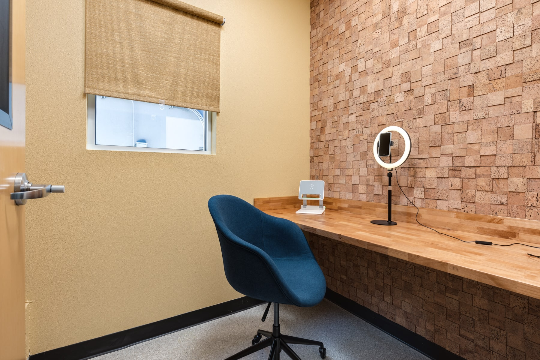 A small room designed to be used as a phone booth. Includes a ring light, laptop stand, and comfortable blue chair.