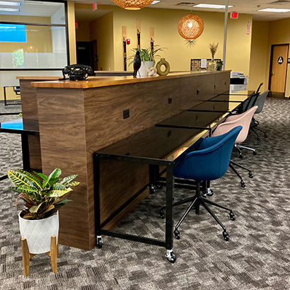 Coworking space shows beautiful wooden divider with several desks and seats. Green plants decorate the space.